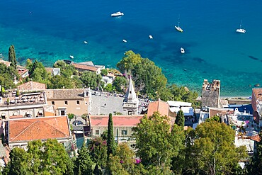 View down steep hillside over rooftops to Piazza IX Aprile and the Ionian Sea below, Taormina, Messina, Sicily, Italy, Mediterranean, Europe