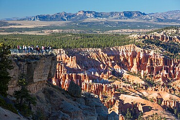 Visitors looking down into Bryce Amphitheatre from the Rim Trail at Bryce Point, Bryce Canyon National Park, Utah, United States of America, North America