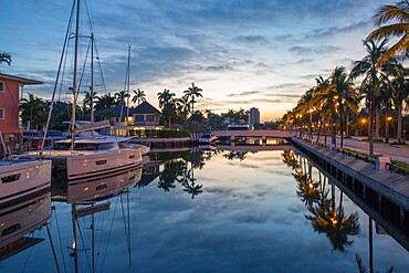 View along tranquil canal at dawn, yachts reflected in still water, Nurmi Isles, Fort Lauderdale, Florida, United States of America, North America