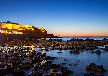 View from rocky shore to the illuminated Fortezza and distant Akrotiri Peninsula, sunset, Rethymno (Rethymnon), Crete, Greek Islands, Greece, Europe