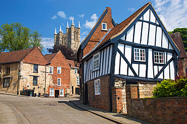 View up cobbled Michaelgate to Lincoln Cathedral, crooked half-timbered house in foreground, Lincoln, Lincolnshire, England, UK