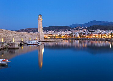 View across the Venetian Harbour at dusk, 16th century lighthouse reflected in water, Rethymno (Rethymnon), Crete, Greek Islands, Greece, Europe