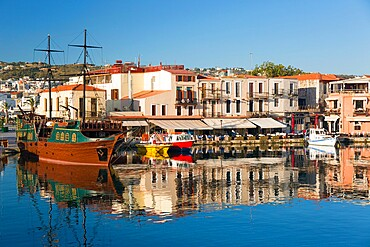 View across the Venetian Harbour, quayside buildings reflected in still water, Rethymno (Rethymnon), Crete, Greek Islands, Greece, Europe