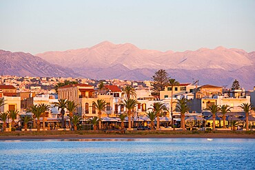 View to the waterfront and distant peaks of the Lefka Ori, sunrise, Rethymno (Rethymnon), Crete, Greek Islands, Greece, Europe