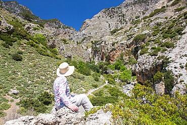 Hiker on rocks admiring view into the Rouvas Gorge, Zaros, Iraklio (Heraklion), Crete, Greek Islands, Greece, Europe