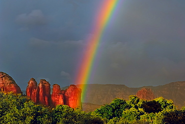 A purely accidental photo of a rainbow intersecting Coffee Pot Rock in Sedona, Arizona, United States of America, North America