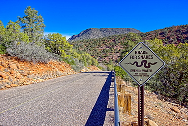 A road leading to Grasshopper Point in Sedona with a warning sign to not run over protected snakes, Arizona, United States of America, North America