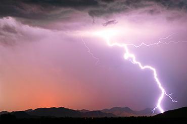 A bright lightning strike illuminating the Buckeye Foothills in Arlington during the 2012 Monsoon season, Arizona, United States of America, North America