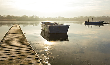 A rowing boat floats adrift on a frozen lake beside an empty walkway at Hornsea Mere, East Yorkshire, Yorkshire, England, United Kingdom, Europe