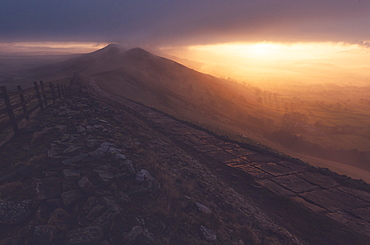 The path on Mam Tor runs off and out of view into a foggy sunrise, Peak District, Derbyshire, England, United Kingdom, Europe