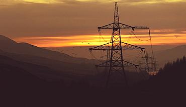 Striking pylons run through a hazy sunset in the Peak District, South Yorkshire, Yorkshire, England, United Kingdom, Europe