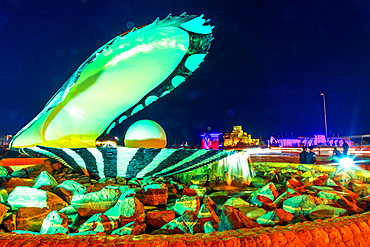 Oyster and Pearl Monument with fountain illuminated at night, celebrating the past pearl industry in Qatar, Doha, Qatar, Middle East