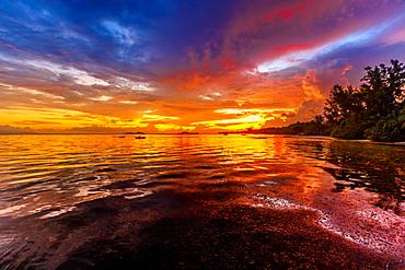 Summer sunset sky reflected in the sea, Grand Anse Fond de Lanse beach on Praslin Island, Seychelles, Indian Ocean, Africa