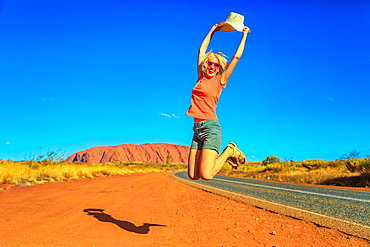 Tourist woman jumping and holding her hat at Uluru (Ayers Rock) in Uluru-Kata Tjuta National Park, UNESCO World Heritage Site, Northern Territory, Central Australia, Pacific