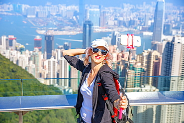 Tourist taking selfie stick picture photo with smart phone enjoying view over Victoria Harbour from viewing platform on top of Peak Tower, Victoria Peak, Hong Kong, China, Asia