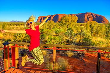 Tourist woman jumping in Uluru-Kata Tjuta National Park, UNESCO World Heritge Site, with Uluru and Kata Tjuta in the background, Northern Territory, Australia, Pacific