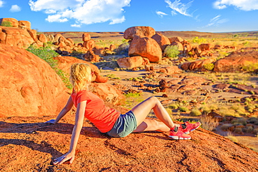 Tourist woman on Nyanjiki Lookout at sunset admiring panoramic views and vibrant colors of gigantic boulders of natural rock formations at Karlu Karlu (Devils Marbles), Northern Territory, Australia, Pacific