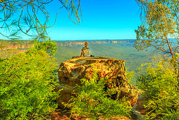 Tourist woman relaxing after hiking and enjoying panoramic views of granite boulders rock formations from Baltzer Lookout in Blue Mountains National Park near Sydney, New South Wales, Australia, Pacific