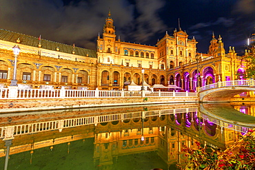 Renaissance building in Plaza de Espana (Spain Square), reflects on channel of Guadalquivir River, illuminated at night, Seville, Andalusia, Spain, Europe