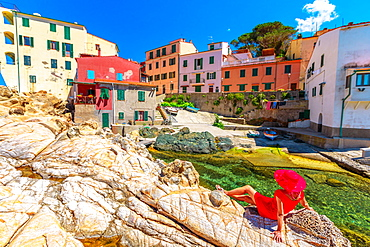 Woman in red dress sitting on cliffs at Marciana Marina in Borgo al Cotone with the famous houses of old village in bay of Marciana Marina promenade, Elba Island, Tuscany, Italy, Europe - 1314-218