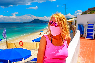 Lifestyle woman with pink surgical mask on roof terrace at Le Ghiaie Beach during Covid-19 pandemic, Elba island, Tuscany, Italy, Europe