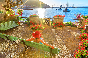Elegant woman in red with hat at Marciana Marina waterfront, the flowery old district called Borgo al Cotone, Elba island, Tuscan Archipelago, Tuscany, Italy, Europe