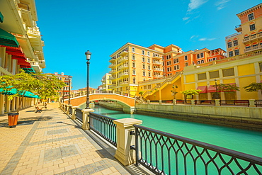 Beautiful Little Venice with canals connected by bridges in Venetian style and colourful houses in picturesque Qanat Quartier, Venice at the Pearl in sunset light, Doha, Qatar, Middle East