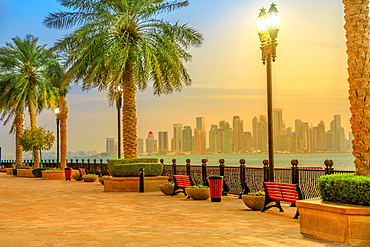 Benches and palm trees along marina walkway in Porto Arabia at the Pearl-Qatar, with skyscrapers of West Bay skyline illuminated at blue hour, Doha, Qatar, Middle East