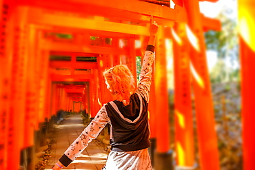 Woman walking beneath red torii gates at Fushimi Inari Shinto shrine, Kyoto, Japan, Asia