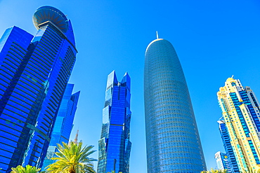 Low angle view of Woqod Tower and Alfardan Towers in West Bay area, modern glassed skyscrapers in Downtown Doha, Qatar, Middle East