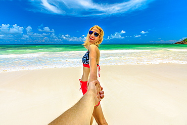 Happy tourist woman in bikini holding hand of her partner, Wild Anse Kerlan, Praslin, Seychelles, Indian Ocean, Africa
