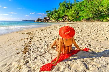 Tourist woman in red sun hat sitting on pristine white beach at sunset, Anse Georgette Beach, Praslin Island, Seychelles, Indian Ocean, Africa