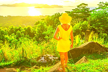 Tourist woman in yellow dress enjoying view of Praslin Island from top viewpoint of La Digue at sunset, Seychelles, Indian Ocean, Africa