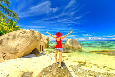 Tourist woman with raised arms in red hat standing on a boulder, Anse Source d'Argent, La Digue, Seychelles, Indian Ocean, Africa