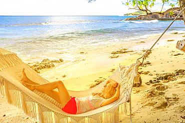 Blonde girl sleeping in a hammock in luxury resort, Felicite Island, Seychelles, Indian Ocean, Africa