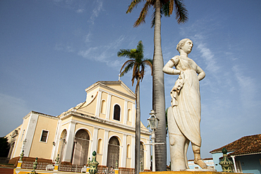Statue in Plaza Mayor, Church of the Holy Trinity (Iglesia de la Santisima Trinidad) in the background, Trinidad, UNESCO World Heritage Site, Cuba, West Indies, Caribbean, Central America