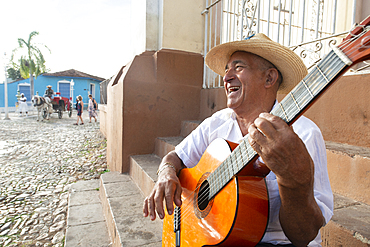 Local man singing and playing his guitar in the Plaza Mayor of Trinidad, Cuba, West Indies, Caribbean, Central America