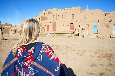 Woman standing in front of Taos Pueblo, UNESCO World Heritage Site, Taos, New Mexico, United States of America, North America