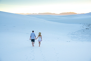 A couple enjoy White Sands National Park at sunset, New Mexico, United States of America, North America