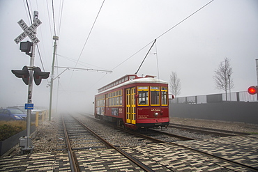 Street car emerging from dense morning fog in the French Quarter of New Orleans, Louisiana, United States of America, North America