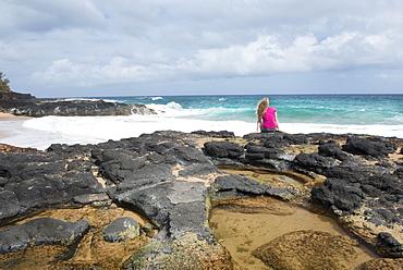 Sitting by a tidal pool on Secret Beach on the Hawaiian island of Kauai, Hawaii, United States of America, North America