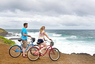 Couple on bikes looking out at the ocean on the shores of Kauai, near Kapaa, Kauai, Hawaii, United States of America, North America