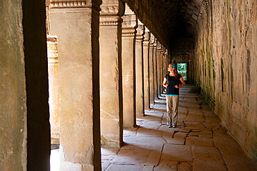 Young woman strolling through the Angkor archaeological complex, UNESCO World Heritage Site, Siem Reap, Cambodia, Indochina, Southeast Asia, Asia