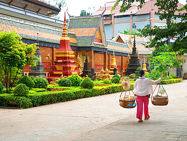 Woman carrying baskets over her shoulders outside a temple in Siem Reap, Cambodia, Indochina, Southeast Asia, Asia