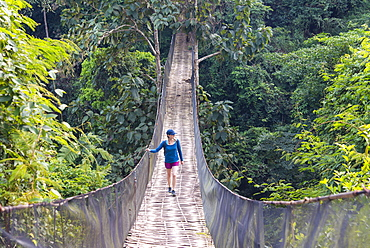 A woman crosses a precarious looking suspension bridge over the jungle in Laos, Indochina, Southeast Asia, Asia