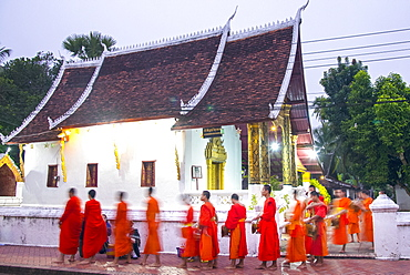 Buddhist monks receive rice from locals during an early morning daily ritual known as Sai Bat (morning alms) in Luang Prabang, Laos, Indochina, Southeast Asia, Asia