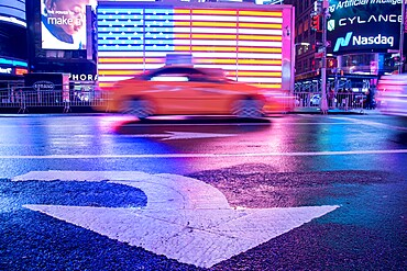 Taxi blurring by an illuminated flag of the United States of America at Times Square, New York City, United States of America, North America