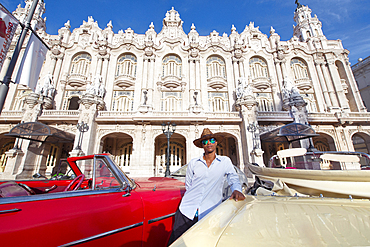 Taxi driver next to his vintage car in front of the Gran Teatro de La Habana, Havana, Cuba, West Indies, Caribbean, Central America