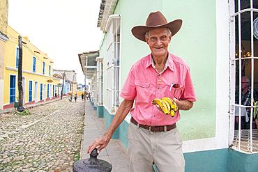 Man selling bananas on a street corner in Trinidad, Cuba, West Indies, Caribbean, Central America