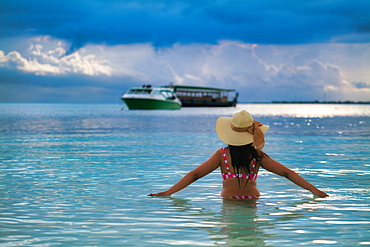 A female tourist in the blue waters of The Maldives, Indian Ocean, Asia